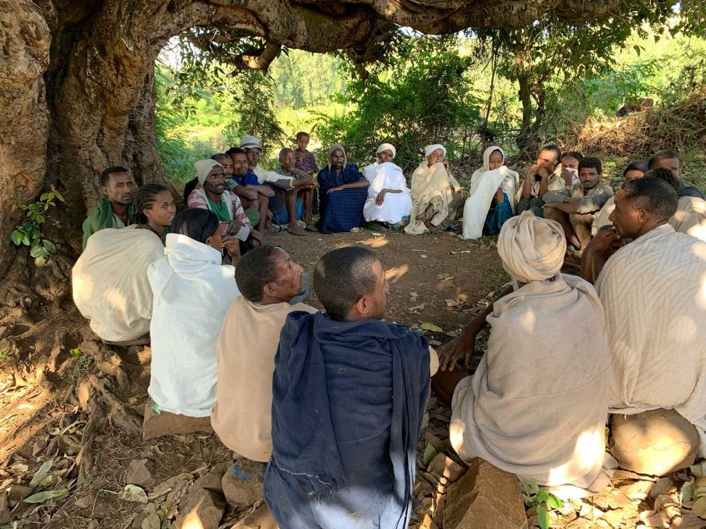 A picture of local villagers having a meeting together.