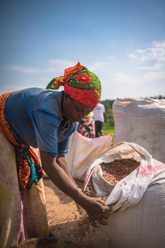 A Rwandan woman with a bag of seeds.